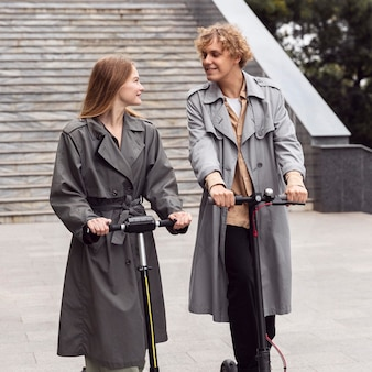 Pareja con scooter eléctrico juntos al aire libre