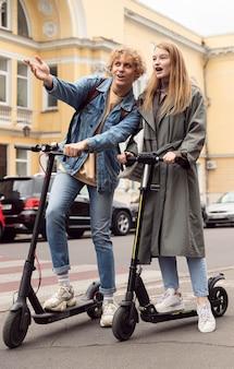 Pareja en scooters eléctricos en la ciudad