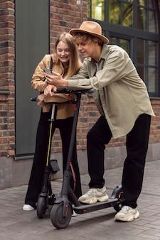 Pareja con scooters eléctricos y smartphone en la ciudad.