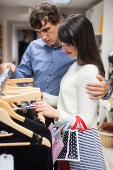 Pareja seleccionando un vestido mientras compra ropa