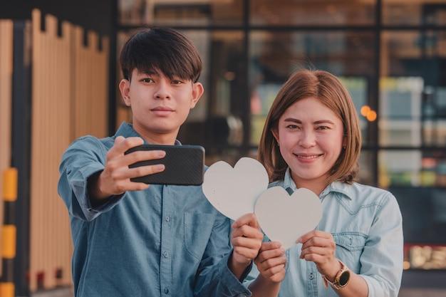 Pareja selfie con teléfono móvil dando corazón de amor
