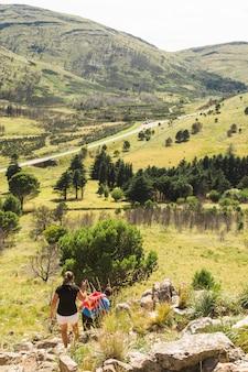 Pareja de senderismo en la colina de piedra cerca del valle