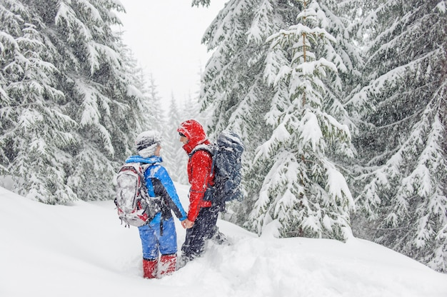 Pareja de senderismo en las montañas nevadas