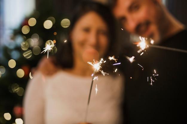 Pareja senior alegre celebración de fuegos artificiales