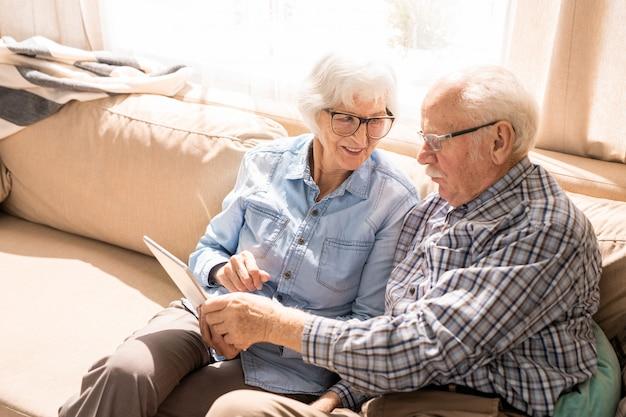 Pareja senior alegre usando tableta en casa