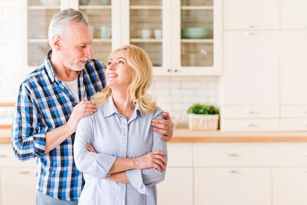 Pareja senior amorosa de pie en la cocina mirando el uno al otro