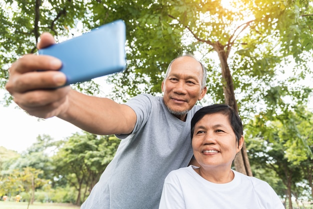 Pareja senior asiática tomando fotos selfie con smartphone.