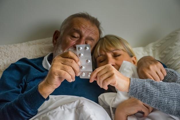 Pareja senior en la cama y manos sosteniendo medicamentos