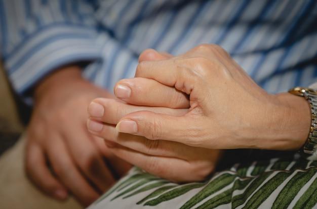 Pareja senior cogidos de la mano mientras se sientan juntos en el sofá en casa