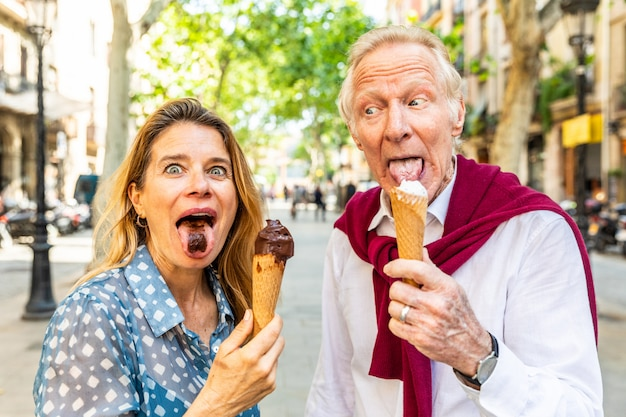 Pareja senior comiendo helado y divirtiéndose en barcelona
