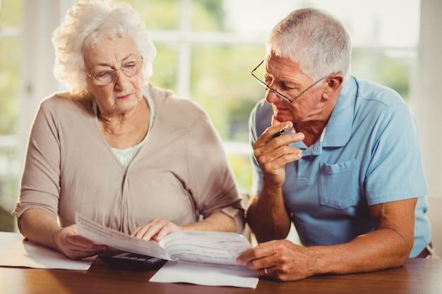 Pareja senior contando facturas en casa