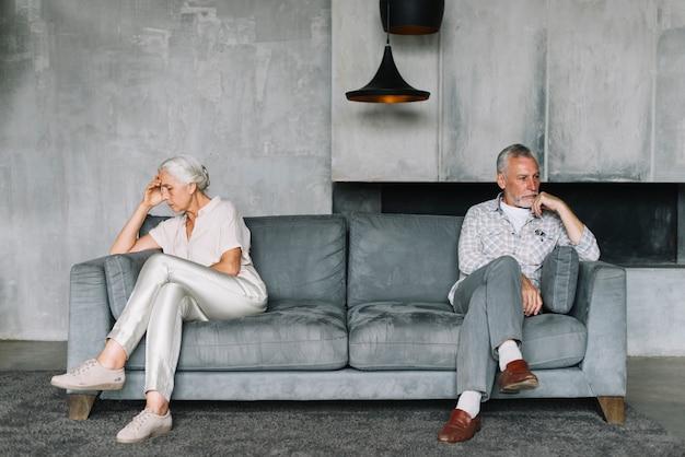 Pareja senior después de una discusión sentado en los extremos opuestos del sofá.