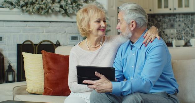 Pareja senior jubilada en casa comprando productos o servicios en línea mediante tableta digital.