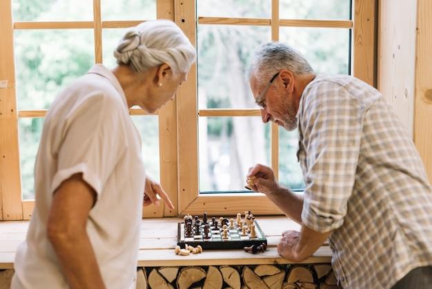 Pareja senior jugando al ajedrez en el alféizar de la ventana
