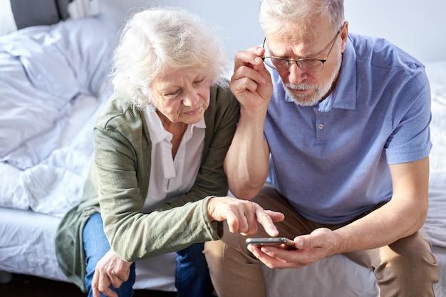Pareja senior mirando fotos de niños en teléfonos inteligentes, surfung net en línea, concepto de tecnología moderna. el hombre y la mujer caucásicos que usan el teléfono móvil comparten las redes sociales juntos en el bienestar del hogar.
