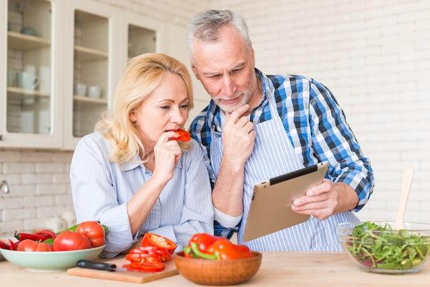 Pareja senior mirando tableta digital mientras prepara la comida en la cocina