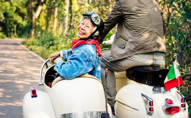 Pareja senior montando un scooter clásico
