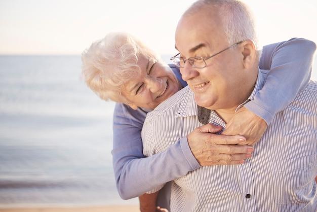 Pareja senior en la playa, la jubilación y el concepto de vacaciones de verano