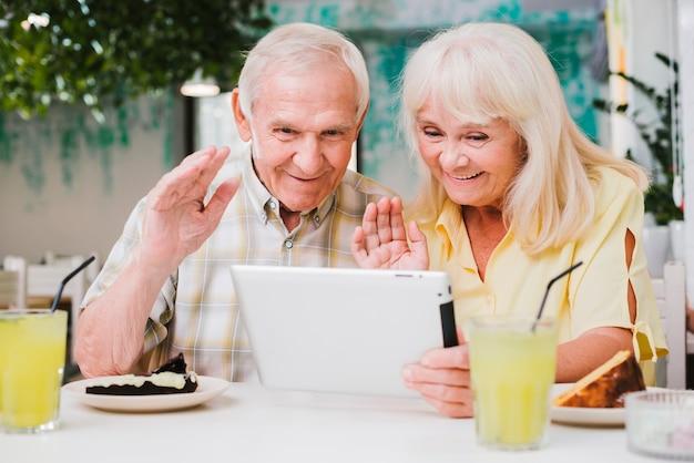 Pareja senior positiva en café con videollamada en tableta