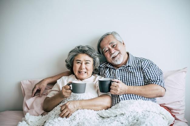 Pareja senior riendo mientras bebe café en el dormitorio
