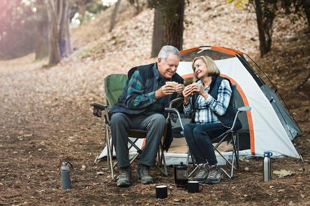Pareja senior romántica haciendo un picnic en el camping