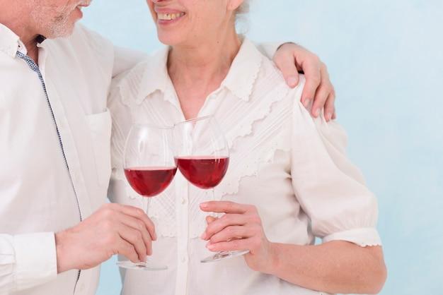 Pareja senior sonriente con la celebración de copa de vino