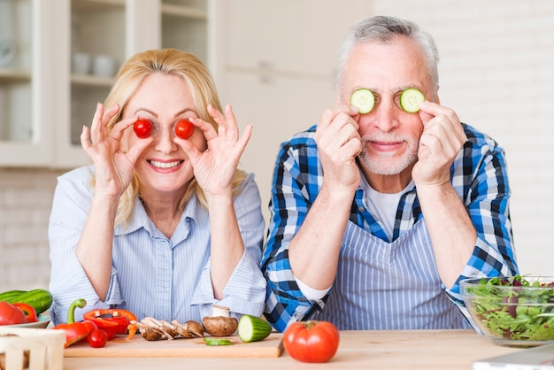 Pareja senior sonriente sosteniendo tomates cherry y rodajas de pepino frente a sus ojos