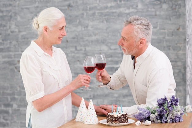 Pareja senior tintineo copa de vino en la fiesta de cumpleaños
