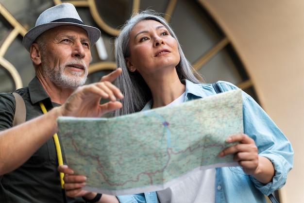 Pareja senior de tiro medio con mapa del mundo