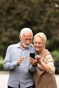 Pareja senior de tiro medio con smartphone