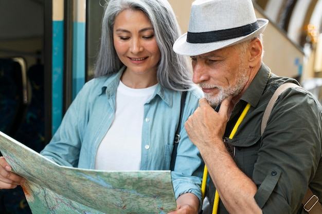 Pareja senior de tiro medio viajando con mapa