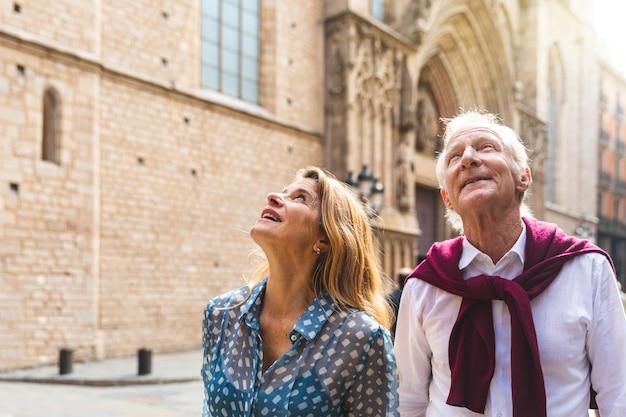 Pareja senior de turistas visitando el casco antiguo de barcelona.
