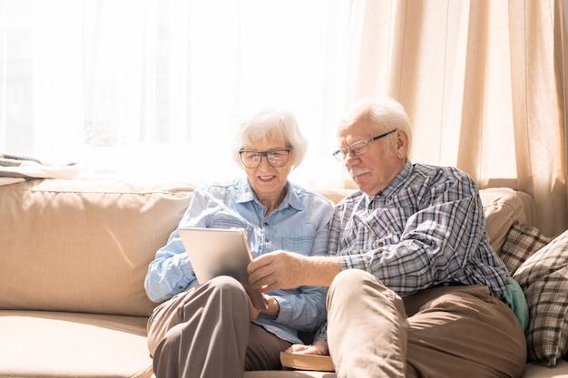 Pareja senior usando tableta en casa