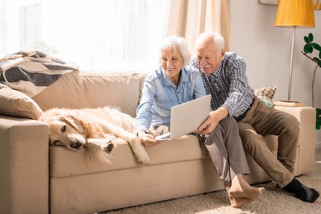 Pareja senior utilizando video chat con perro