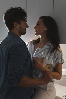 Pareja sensual bebiendo vino y relajándose en casa