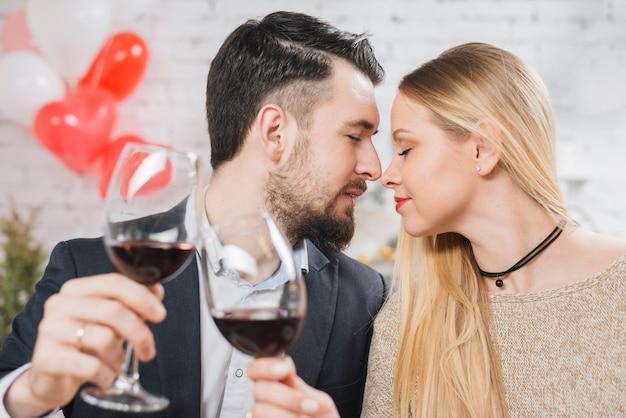 Pareja sensual tintineo con vino