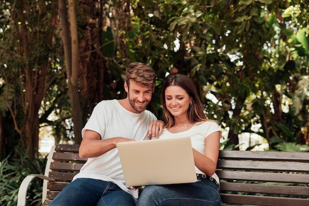 Pareja sentada en un banco con laptop