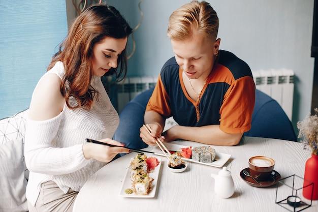 Pareja sentada en un café y comiendo sushi