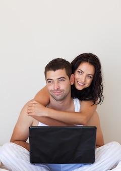 Pareja sentada en una cama con la computadora portátil