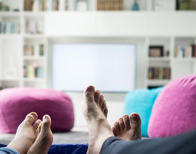 Pareja sentada en casa viendo tv