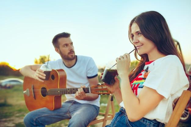 Pareja sentada y descansando en la playa tocando la guitarra en un día de verano cerca del río. amor, familia feliz, vacaciones, viajes, concepto de verano. hombre y mujer caucásicos