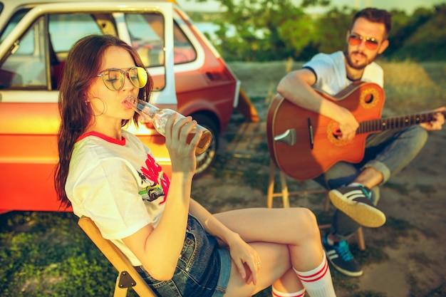 Pareja sentada y descansando en la playa tocando la guitarra en un día de verano cerca del río. amor, familia feliz, vacaciones, viajes, concepto de verano.