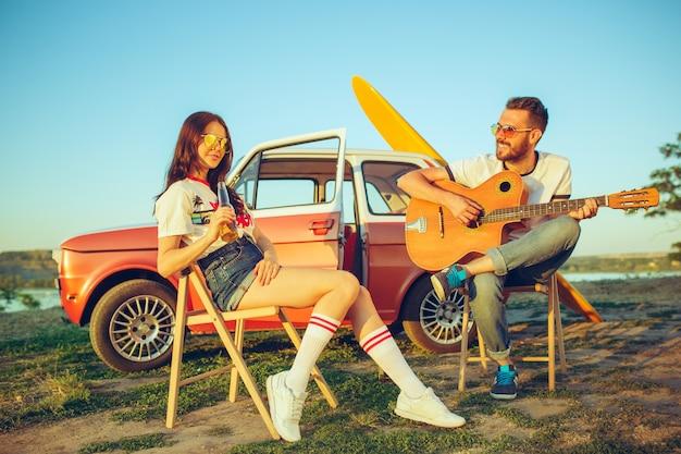 Pareja sentada y descansando en la playa tocando la guitarra en un día de verano cerca del río. hombre y mujer caucásicos