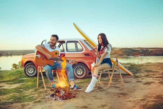 Pareja sentada y descansando en la playa tocando la guitarra en un día de verano cerca del río
