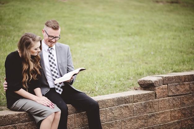 Pareja sentada en un jardín y leyendo un libro juntos con amor