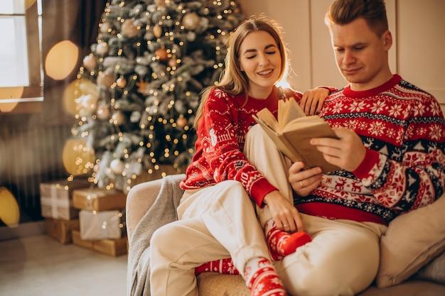 Pareja sentada junto al árbol de navidad y leyendo un libro