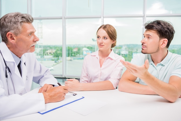 Pareja sentada en la oficina y hablando con el practicante.
