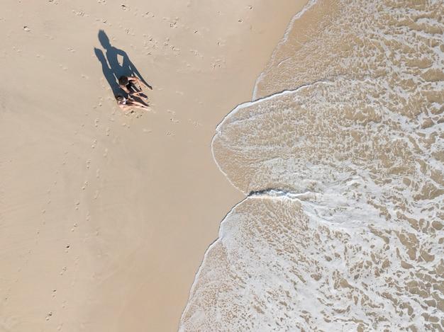 Pareja sentada en la orilla del mar cerca de las olas de espuma
