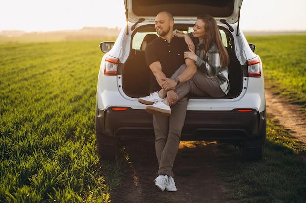Pareja sentada en la parte trasera del automóvil en el campo