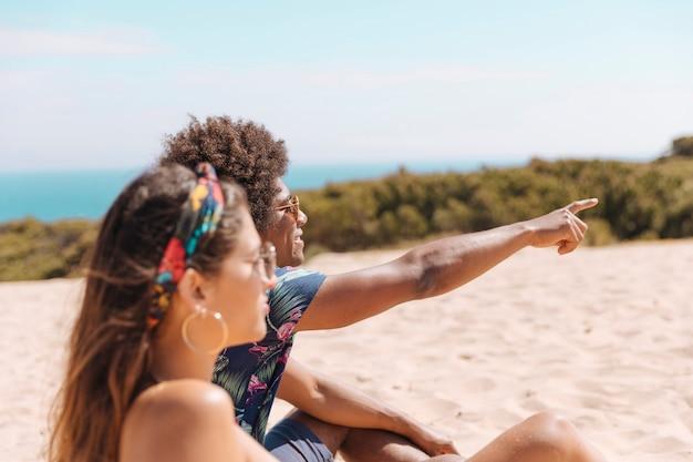 Pareja sentada en la playa y chico mostrando algo lejos a chica